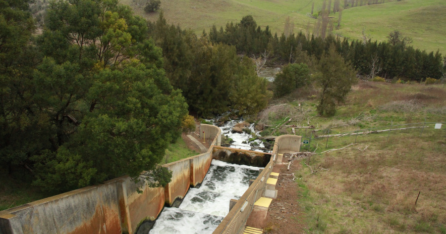 treated water discharging into a river via a weir